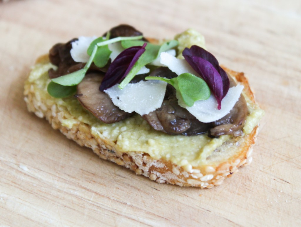 Leek pesto crostini topped with roasted mushrooms, shaved parmesan, and micro-greens