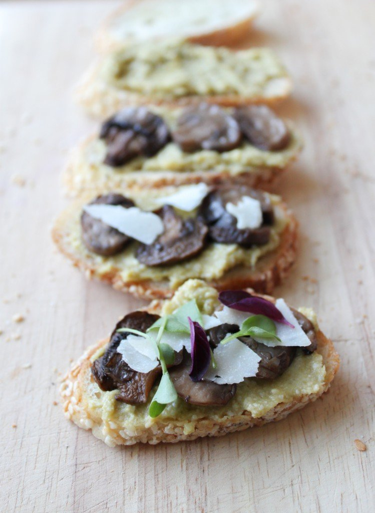 Leek pesto crostini with roasted mushrooms, shaved parmesan, and micro-greens