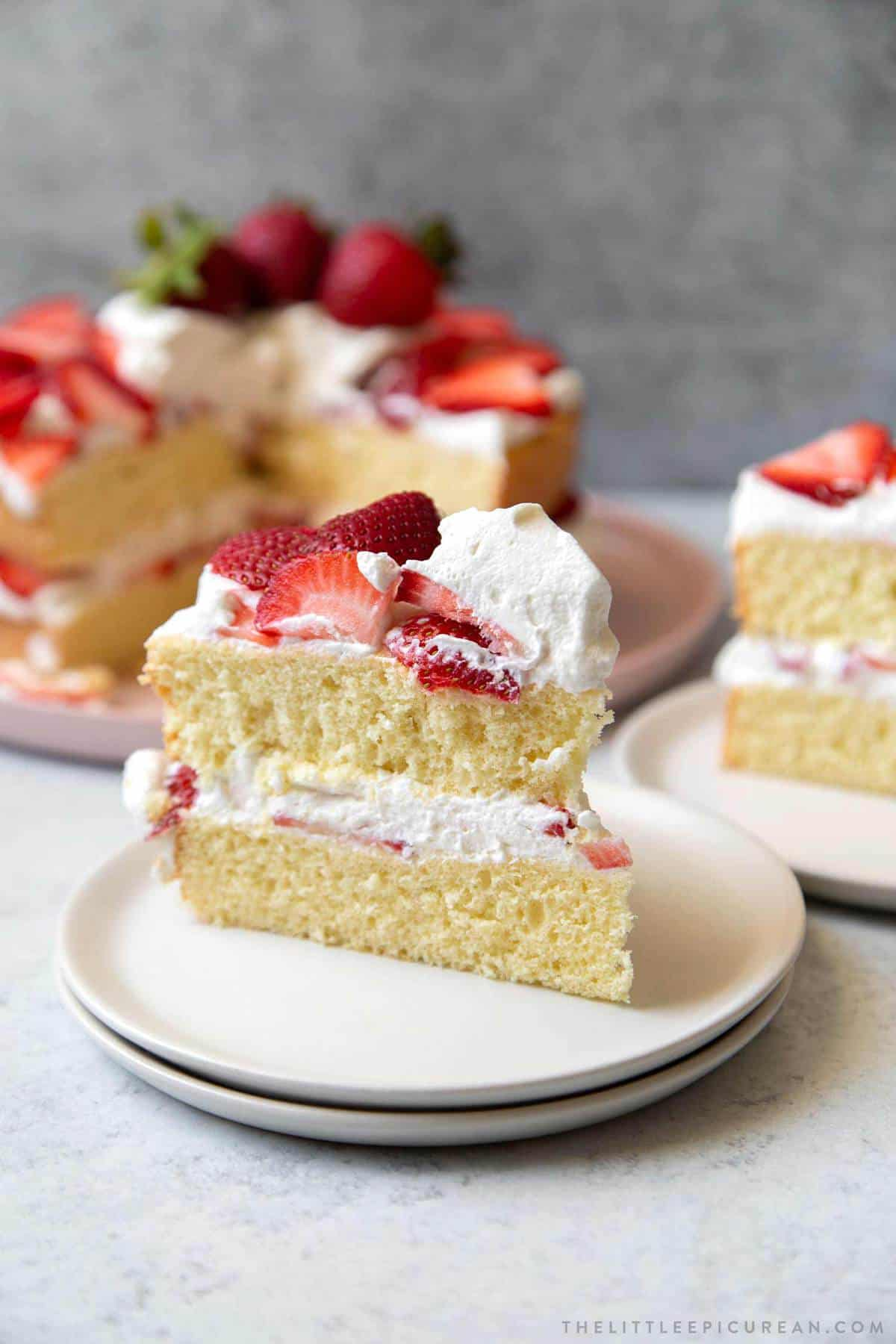 strawberry cake slice with whipped cream frosting.