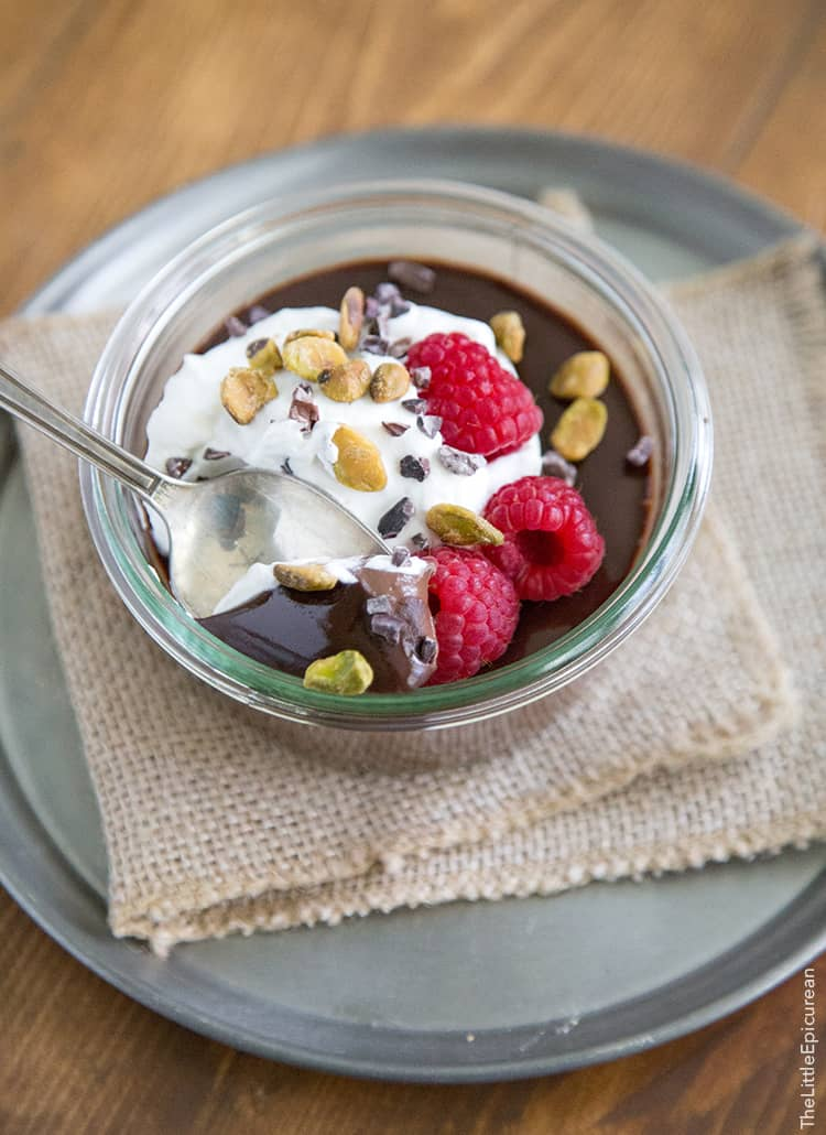 Chocolate Pots de Creme with honey whipped cream, raspberries, pistachios and cocoa nibs