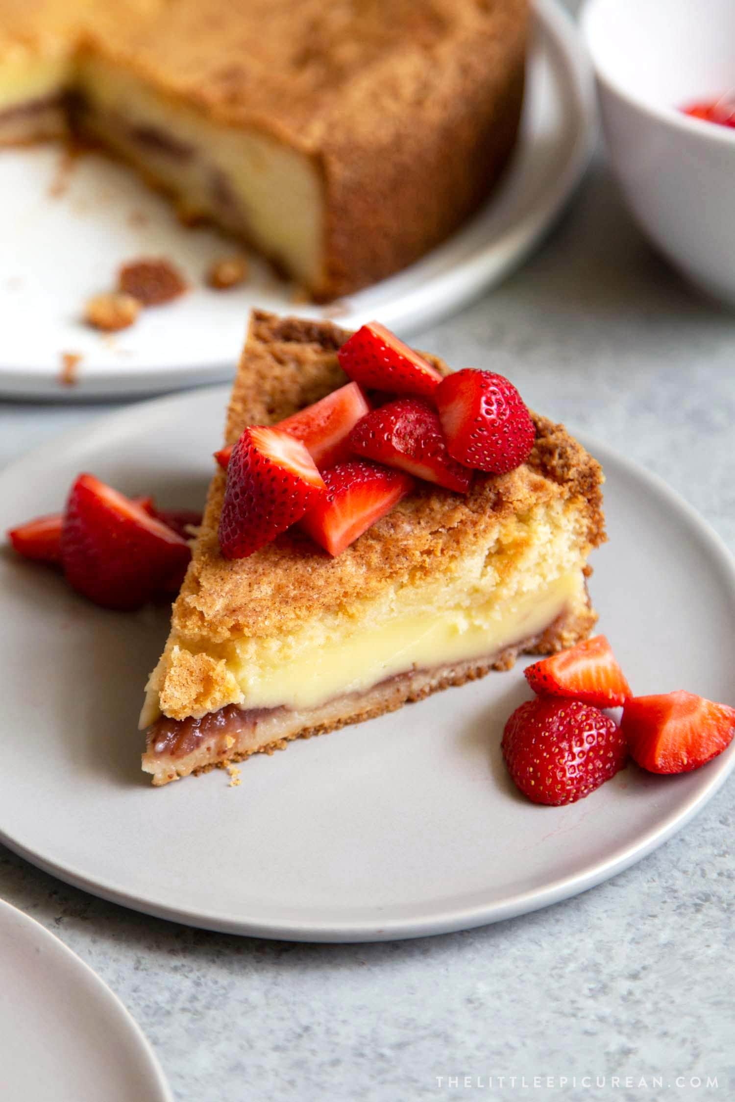 Basque Cake served with fresh strawberries. Basque cake is a buttery cake with a pastry cream filling.