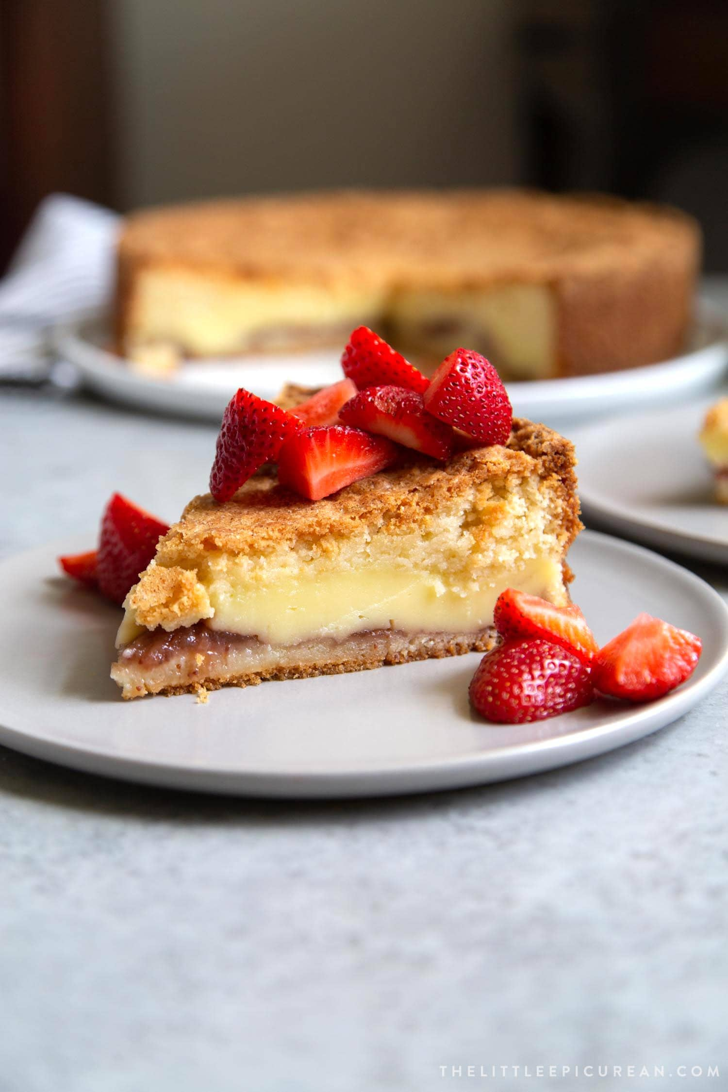 Slice of Basque Cake topped with fresh strawberries. Basque Cake is a buttery cake with strawberry jam and pastry cream filling.