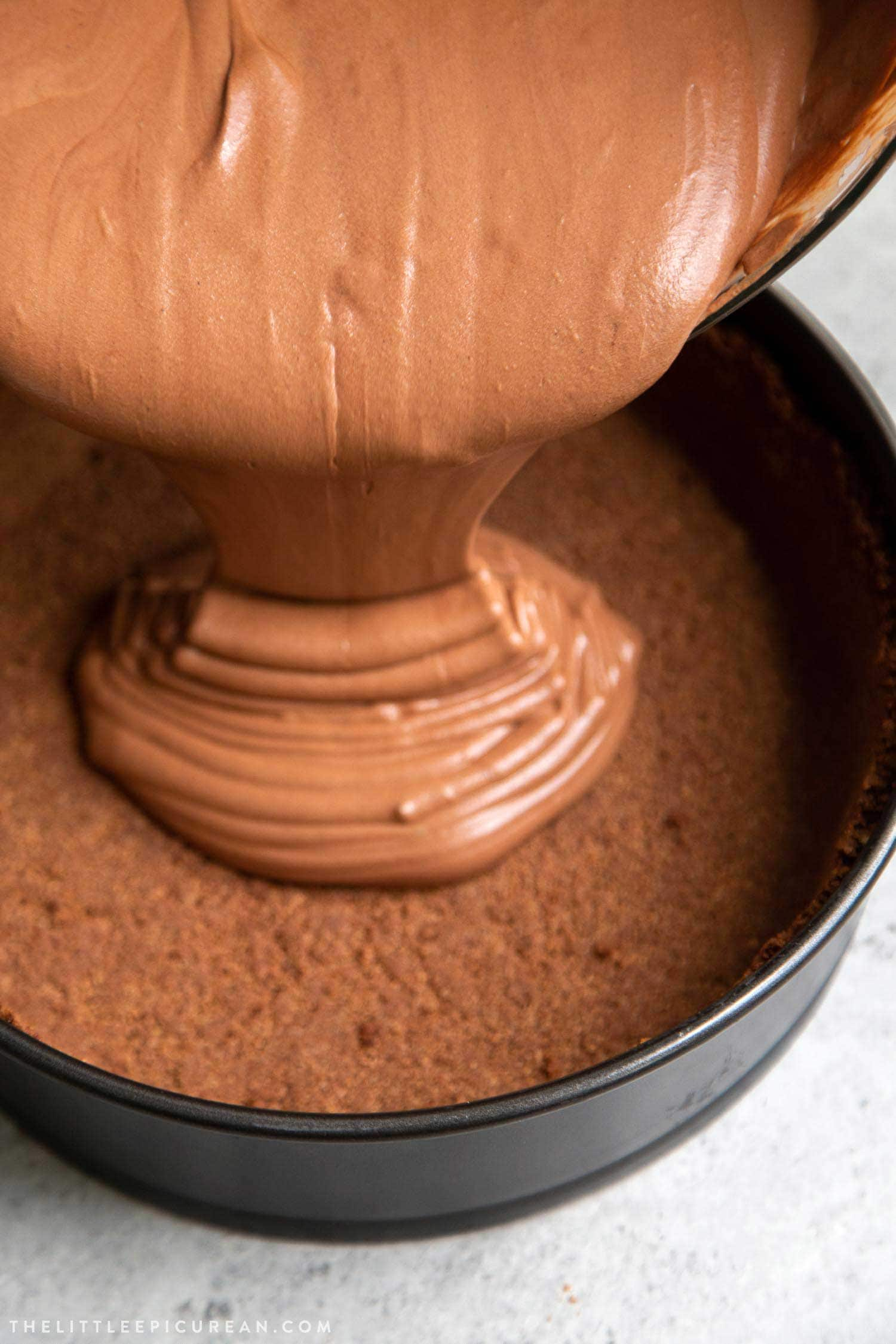 Pouring chocolate mousse into chocolate graham cracker pie shell