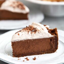 Slice of Chocolate Mousse Pie. Chocolate graham cracker crust filled with chocolate mousse and topped with whipped cream and chocolate shavings.
