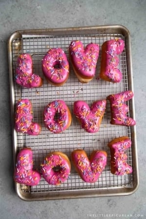 Letter Donuts with pink glaze and rainbow sprinkles. Send your loved ones using donuts!
