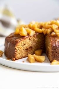 Apple Ginger Cake. Moist ginger cake is flavored with fresh grated ginger and candied ginger pieces. The baked cake is topped with ginger spiced apples and a drizzle of caramel.