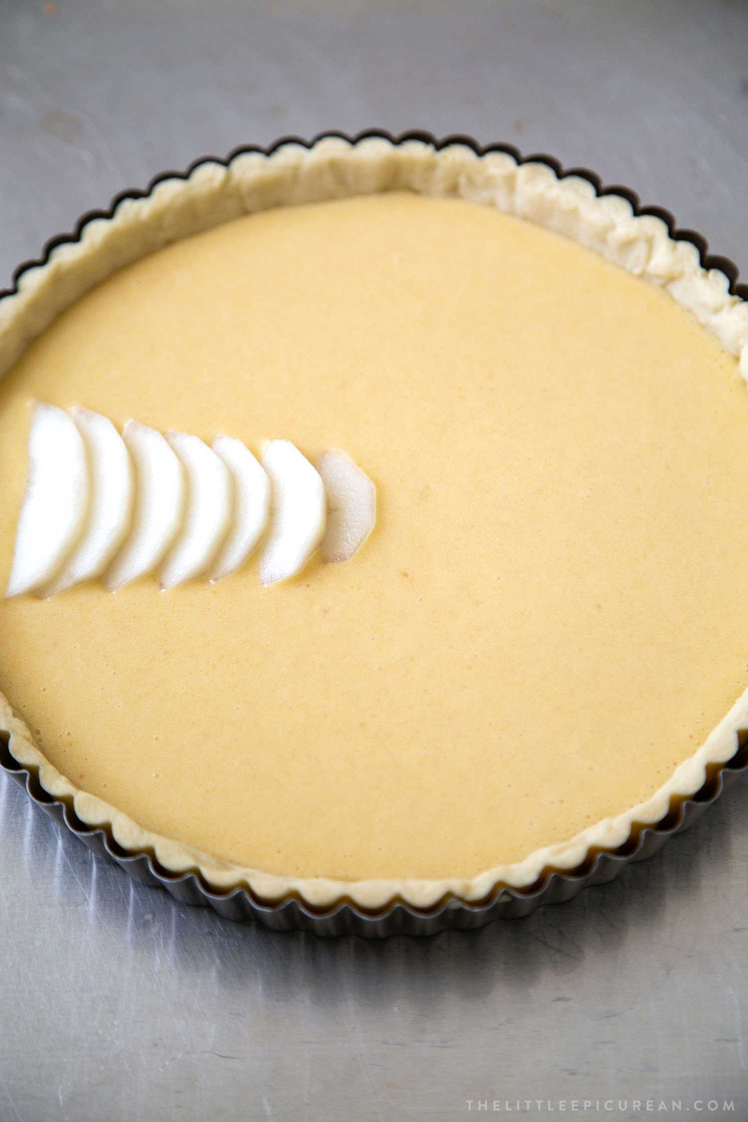 Pear Frangipane Tart. Pour homemade frangipane filling into par-baked tart shell. Then, arrange sliced pears and almonds on top.