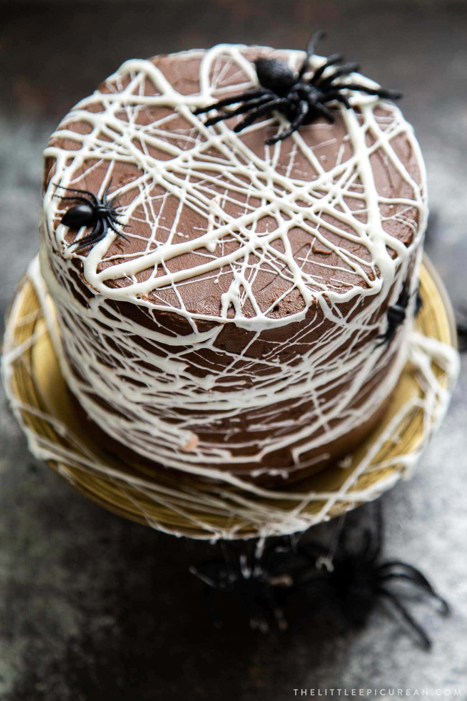Chocolate Spider Web Cake. Three layer chocolate cake frosted with simple chocolate buttercream and decorated with marshmallow spider webs. It's the perfect Halloween treat!