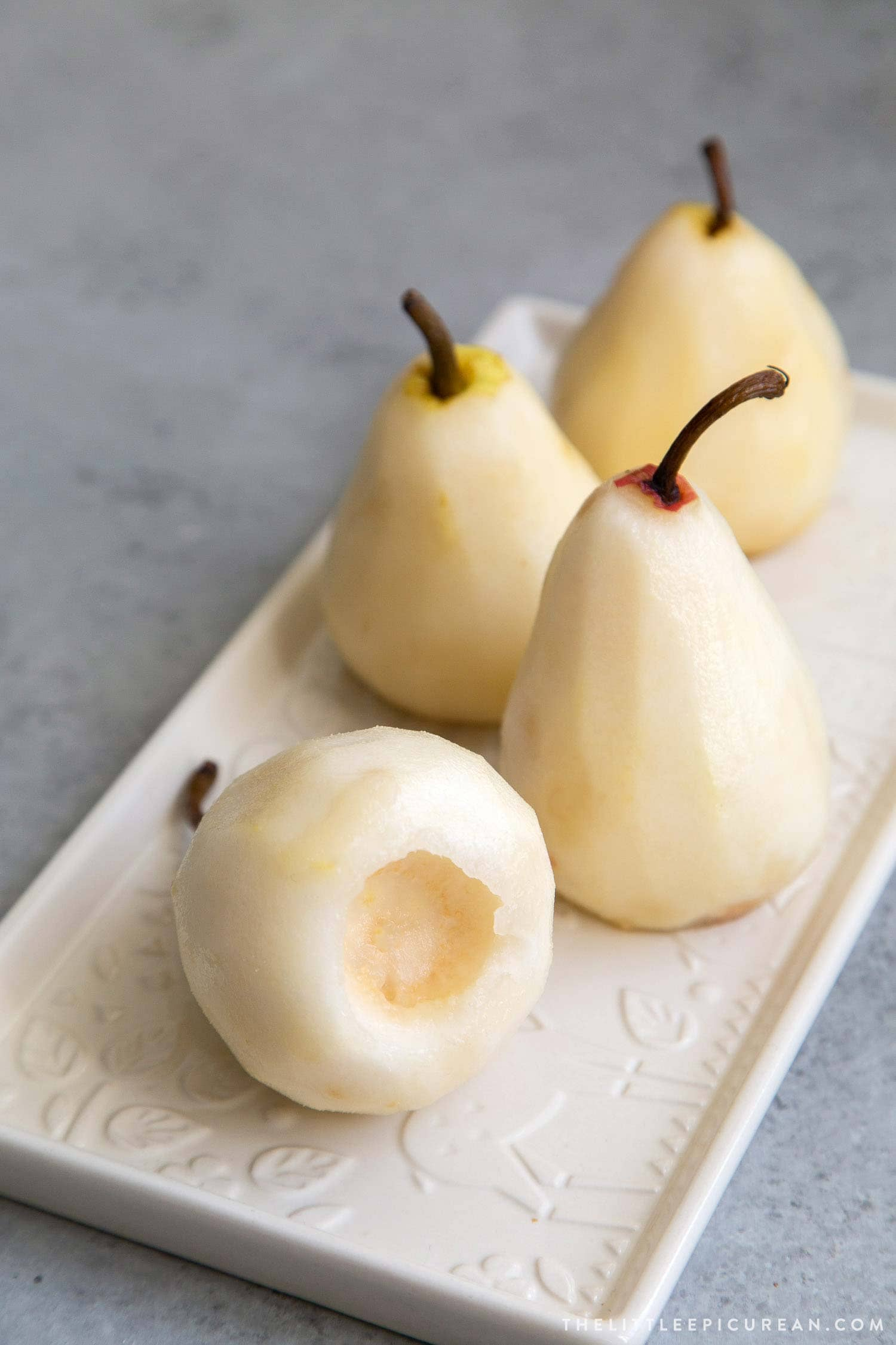 How to Poach Pears: peel pears, slice off 1/4-inch off bottom to flatten. Core out seeds from the bottom of pear.