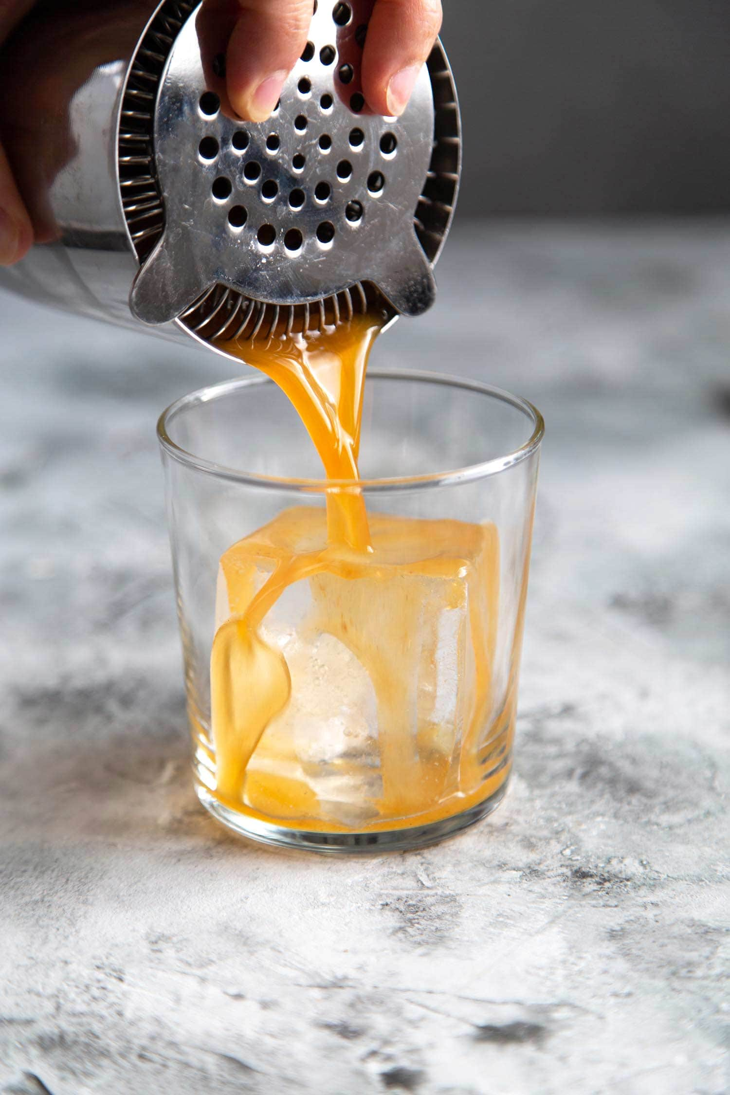 Mix autumn harvest cocktail (pumpkin bourbon cocktail) in a Boston shaker. Then, strain into serving glass.
