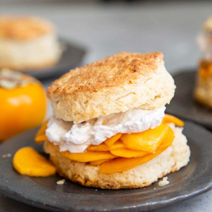 Coconut Persimmon Shortcake. A new spin strawberry shortcake. This dessert features coconut milk shortcake biscuits filled with sliced persimmons and coconut whipped cream. #persimmons #fuyupersimmons #fallbaking #shortcake #biscuits