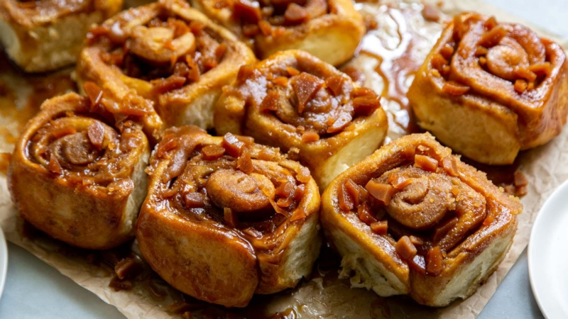 Toffee Sticky Buns. These warm and fluffy buns are filled with cinnamon sugar, coated with a sweet molasses glaze, and topped with chopped toffee bits! #breakfast #brunch #holidays #toffee #stickybuns