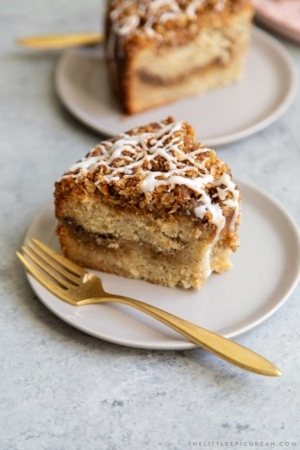 Banana Crumb Cake Slice. Moist banana cake with cinnamon sugar filling topped with walnut oat crumble topping. Finished with maple glaze icing.