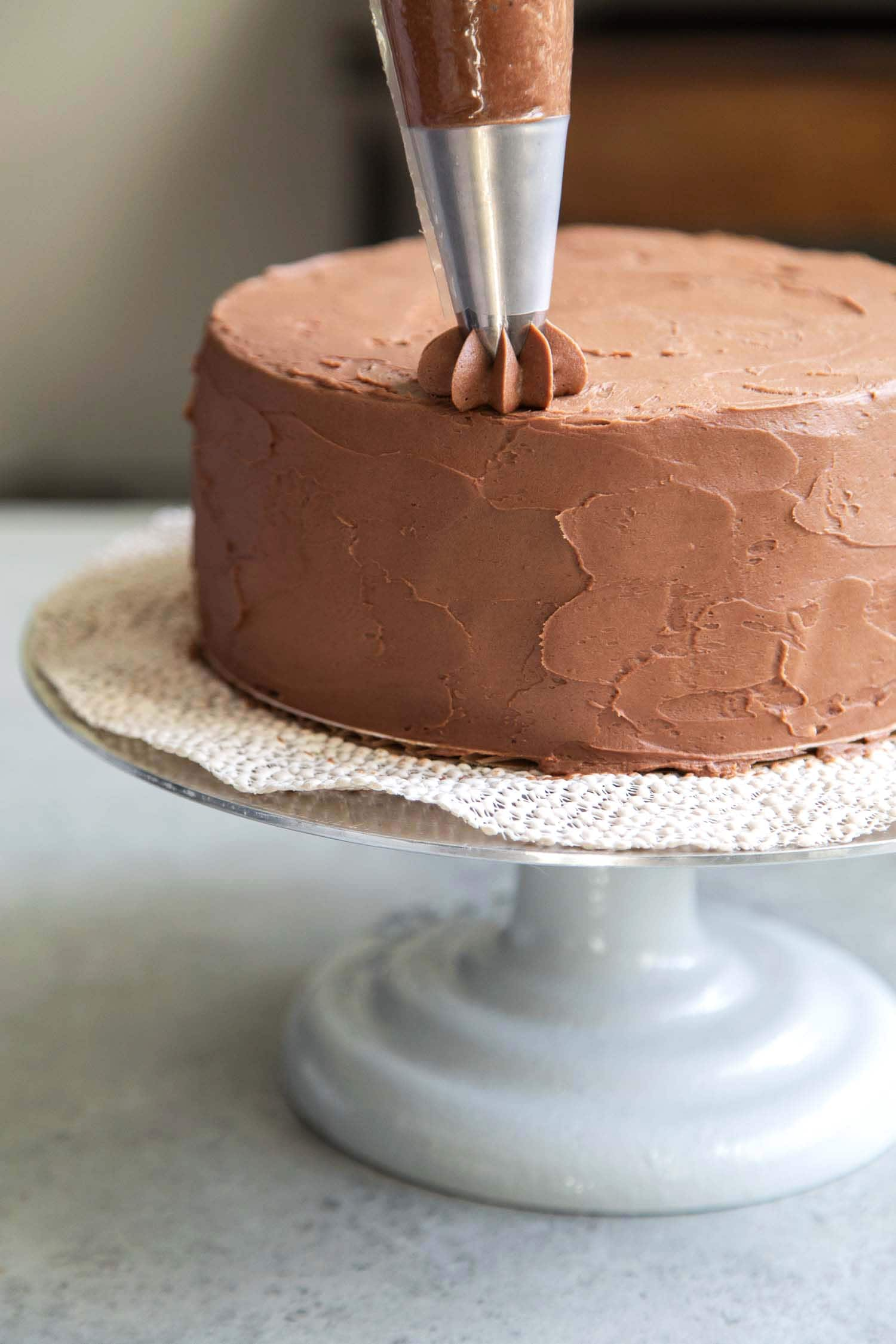 Use a star tip to decorate classic chocolate cake with buttercream.