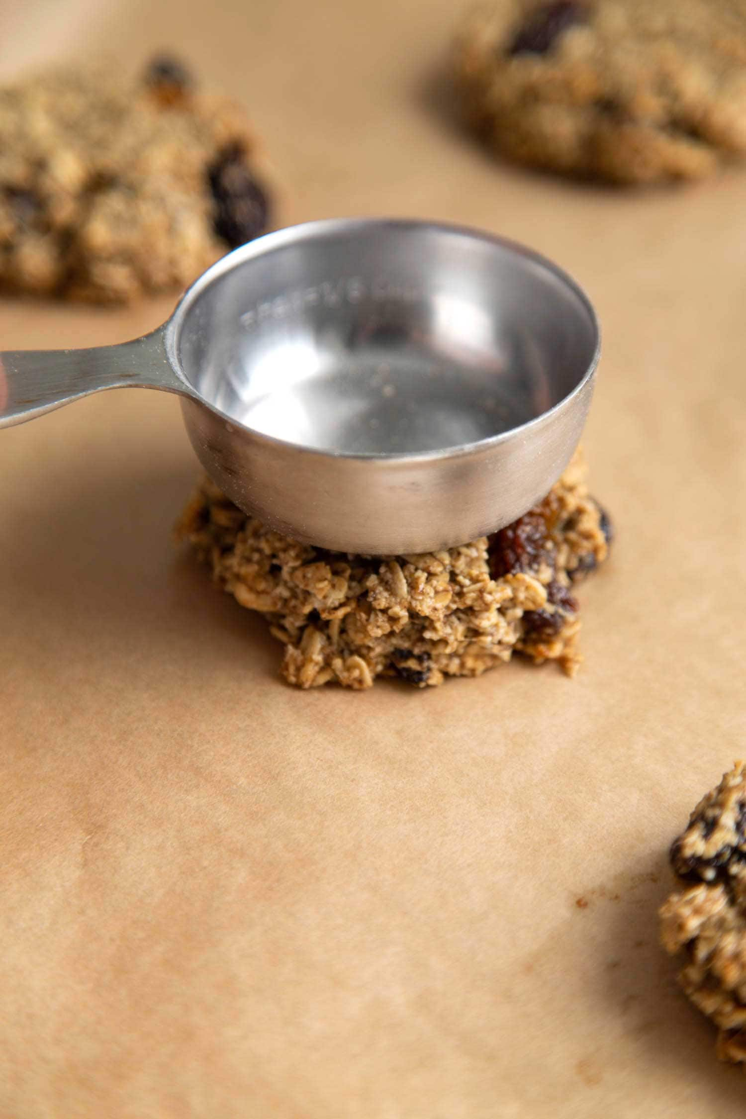 Flatten vegan oatmeal raisin cookie dough before baking