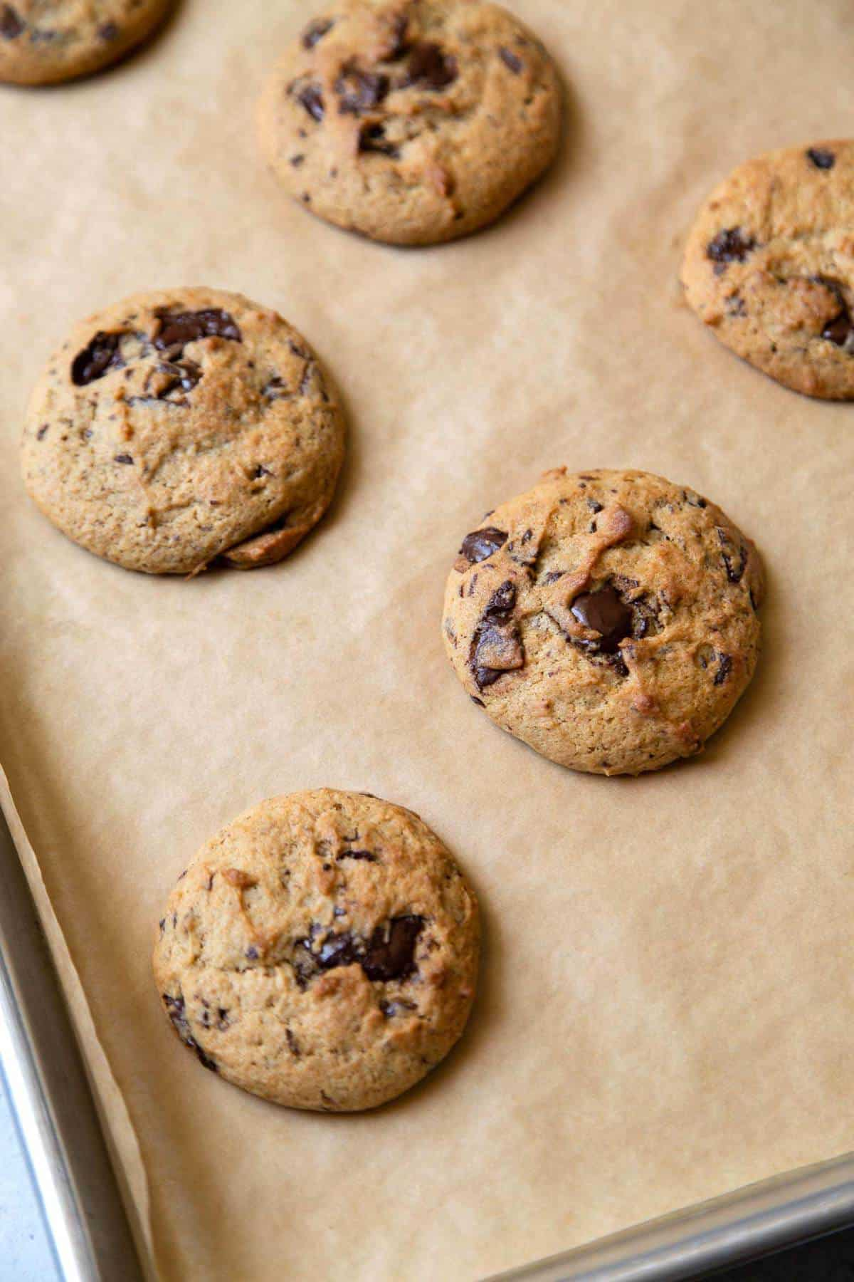 Banana chocolate chip cookies on parchment lined sheet tray.
